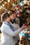 Femmes mûres choisissant des décorations au marché de Noël Photos stock