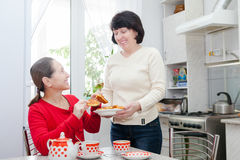 Femmes mûres parlant à la table de cuisine Photographie stock libre de droits