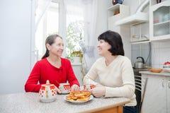 Femmes mûres parlant dans la cuisine Photos libres de droits