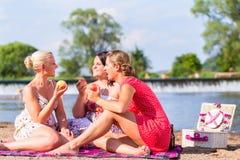Femmes mangeant du fruit au pique-nique de plage de rivière Photo stock
