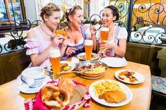Femmes mangeant le déjeuner dans le restaurant bavarois Photographie stock libre de droits
