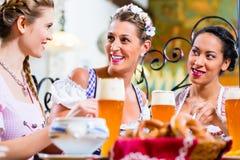 Femmes mangeant le déjeuner dans le restaurant bavarois Image stock