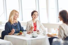 Femmes mangeant le dessert et parlant au restaurant Images libres de droits