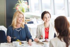 Femmes mangeant le dessert et parlant au restaurant Photos libres de droits