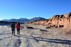 Femmes marchant à la formation de roche de Piedras Rojas du désert d'Atacama, au Chili Photo stock