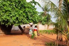Femmes marchant à la maison de la ville au Bénin photographie stock
