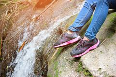 Femmes marchant avec des jeans et des chaussures d'espadrille et fond de cascade, voyage de concept, doux et foyer choisi Photo stock