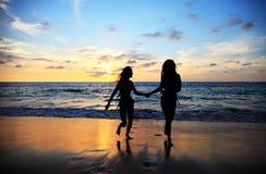 Femmes marchant sur la plage de coucher du soleil Photos libres de droits