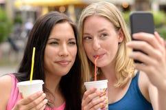 Femmes mignonnes avec des boissons prenant l'autoportrait Image libre de droits