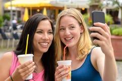 Femmes mignonnes avec des boissons prenant l'autoportrait Photo libre de droits