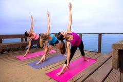 Femmes minces attirantes d'ajustement de retraite extérieure d'emplacement de rangée de classe de yoga de pose d'alignement Photographie stock libre de droits
