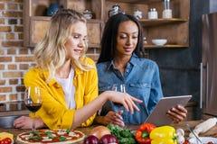 Femmes multi-ethniques à l'aide du comprimé numérique tout en faisant cuire ensemble dans la cuisine Photo stock