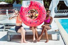 Femmes multi-ethniques heureuses posant avec le beignet gonflable près de la piscine Images libres de droits