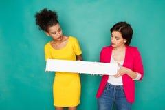 Femmes multi-ethniques joyeuses au fond de studio d'azur Image stock