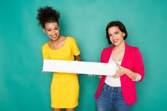 Femmes multi-ethniques joyeuses au fond de studio d'azur Photographie stock libre de droits