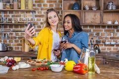 Femmes multi-ethniques prenant le selfie tout en buvant du vin et préparant la pizza ensemble Photos libres de droits