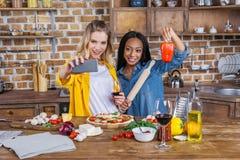 Femmes multi-ethniques prenant le selfie tout en buvant du vin et préparant la pizza ensemble Photographie stock