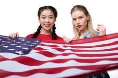 Femmes multi-ethniques regardant l'appareil-photo et tenant le drapeau des Etats-Unis d'isolement sur le blanc, célébration de Jo Image stock