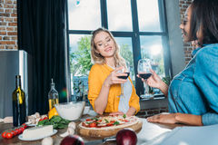 Femmes multi-ethniques tenant des verres de vin tout en mangeant de la pizza à la maison Image libre de droits