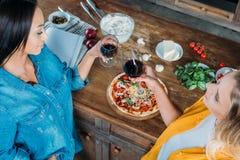 Femmes multi-ethniques tenant des verres de vin tout en mangeant de la pizza à la maison Images libres de droits