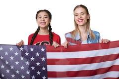 Femmes multi-ethniques tenant le drapeau des Etats-Unis d'isolement sur le blanc, célébration de Jour de la Déclaration d'Indépen Photo libre de droits