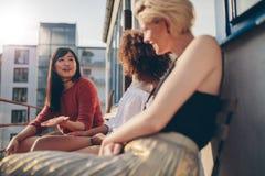 Femmes multiraciales détendant dehors dans un balcon Image libre de droits