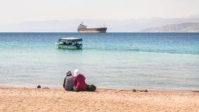 Femmes musulmanes sur la plage urbaine dans le jour d'hiver ensoleillé Image stock
