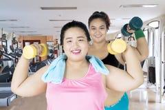 Femmes obèses heureuses s'exerçant avec des haltères Image stock