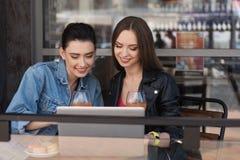 Femmes observant quelque chose sur un carnet Image stock