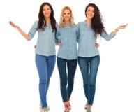 3 femmes occasionnelles heureuses marchant et te souhaitant la bienvenue Images stock