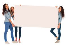 3 femmes occasionnelles heureuses présent un grand conseil vide Photographie stock