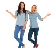 2 femmes occasionnelles heureuses te souhaitant la bienvenue Photographie stock