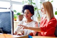 Femmes ou étudiants heureux avec l'ordinateur dans le bureau Photos libres de droits