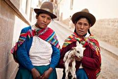 Femmes péruviennes dans la robe authentique avec une chèvre dans Cusco, Pérou Photos stock