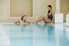 Femmes parlant au bord de la piscine Photos stock