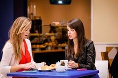 Femmes parlant tout en ayant le café et des casse-croûte à un café Image stock