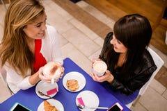 Femmes parlant tout en ayant le café et des casse-croûte Images stock