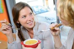 Femmes partageant de la nourriture de cuvette Photo stock