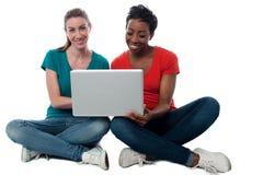 Femmes passant en revue sur l'ordinateur portable Photos libres de droits