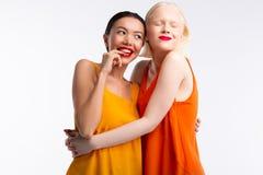Femmes portant les robes lumineuses se sentant vraiment heureuses ensemble image libre de droits
