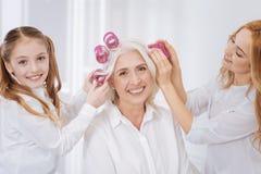 Femmes positives à l'aide des bigoudis de cheveux Images stock
