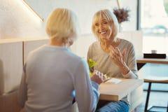 Femmes positives avec plaisir appréciant leur déjeuner Image stock