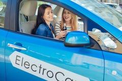 Femmes positives avec plaisir s'asseyant dans la voiture Images stock
