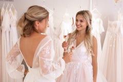 Femmes positives avec plaisir se tenant avec des verres de champagne photographie stock