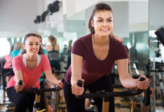 Femmes positives de la formation différente d'âge sur des vélos d'exercice Photographie stock libre de droits