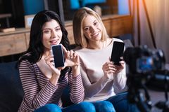 Femmes positives gaies tenant leurs smartphones Images libres de droits