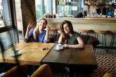 Femmes positives s'asseyant au café avec des tasses de café et de sourire Photos libres de droits