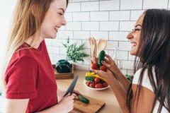 Femmes préparant la nourriture jouant avec des légumes dans la cuisine ayant l'amusement Photos stock
