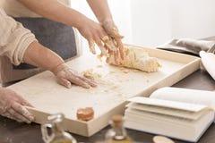 Femmes préparant une pâte sur le panneau de pâtisserie photo stock