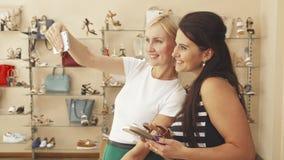 Femmes prenant des selfies dans la boutique de chaussure banque de vidéos